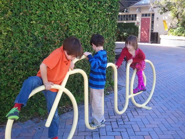 "Whimsical Bike Rack: Whimsical bike rack serves double duty as a play structure when not being used for its ""intended"" purpose."